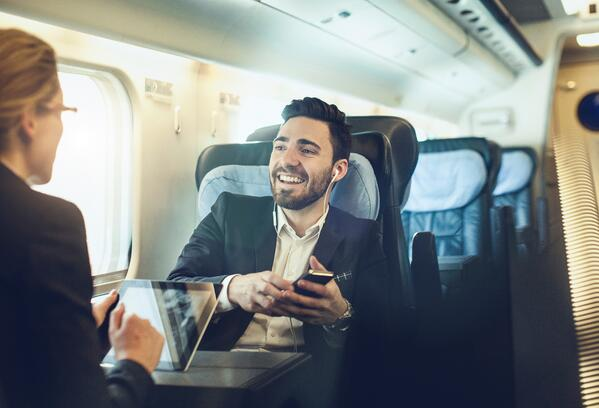 Business people travelling on train with mobile devices-1