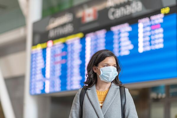 Female traveller at airport in face mask - resized